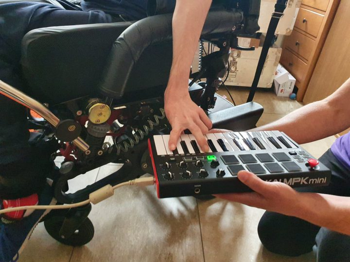 Outreach Music Studio - keyboard midi controller being played by disabled musician.