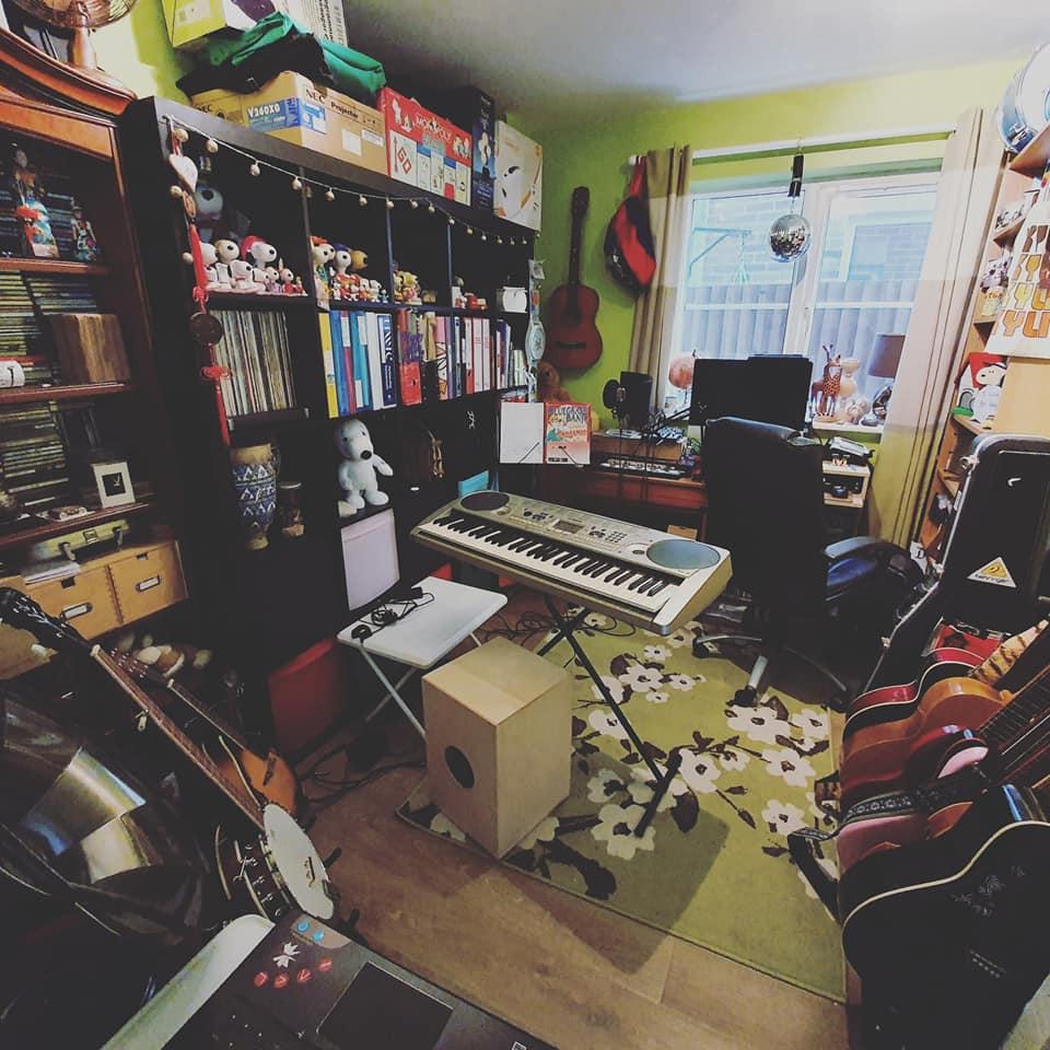 Outreach Music Studio with keyboard, cajon drum, bango, and guitar rack with 7 guitars.